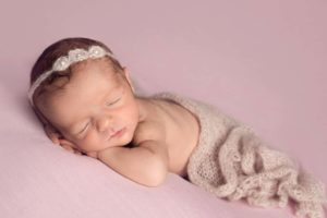 Sleeping baby with lanugo at her newborn photoshoot